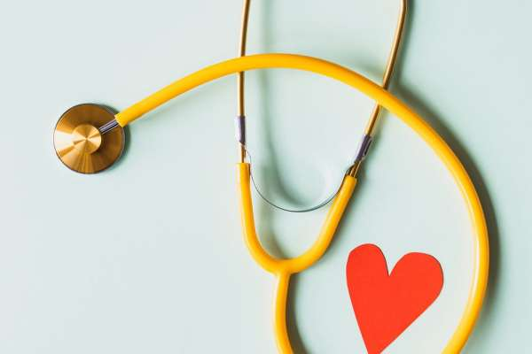 Yellow stethoscope and red paper heart